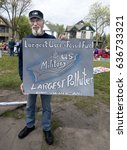 Small photo of MINNEAPOLIS, MINNESOTA - MAY 07, 2017: Man holding poster accusing the US military of being the biggest polluter at the 43rd Annual MayDay Parade.