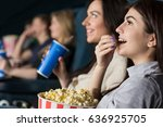 Beautiful young girls laughing eating popcorn watching a film together at the movie theatre copyspace leisure hobby activity friends girlfriends youth positivity happiness smiling eating snacks food