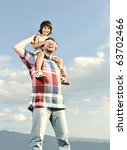 Young father and his son on back, piggyback, pica-boo playing, outdoor scene, love and care - stock photo