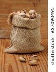 pistachios in sack on wooden... | Shutterstock . vector #637090495