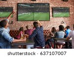 Stock photo friends watching game in sports bar on screens celebrating 637107007