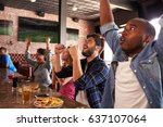 Stock photo friends at counter in sports bar watch game and celebrate 637107064