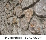 Small photo of Background. The wall of multi-coloured stones agglomerated with cement mortar