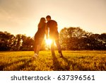 happy couple at sunset in park... | Shutterstock . vector #637396561