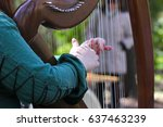 Stock photo girl in green dress plays on a celtic harp in the summer garden 637463239