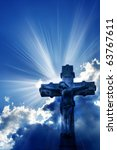 beams of sunlight coming out from behind clouds and a Christian cross - stock photo