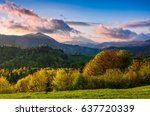 mountain rural area in springtime. agricultural fields on hills with forest. beautiful and vivid countryside landscape with cloudy sky at sunset. - stock photo