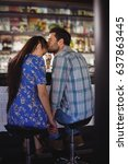 Small photo of Affectionate man holding hands while kissing woman at counter in restaurant