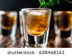 Small photo of Pouring Whiskey Shots with ice on dark wooden surface.