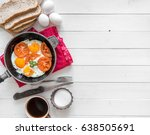 Small photo of Eggs cooked overeasy with fried tomatoes and parsley, homemade bread, additional text space left, topview
