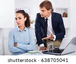 Small photo of Dreary subordinate woman being accused to making mistake by man colleague in company office