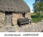Bench By Thatched Roof Leanach...