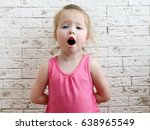 Small photo of Little girl sings in the background of a brick wall. The child opens his mouth and tries to sing. A child's voice.