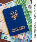 Small photo of Ukrainian passport for travel abroad on a background of euro banknotes (abolition of Schengen visas for Ukrainian - concept)