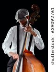 Small photo of Hipster playing double bass, close-up. Looking down, wearing white shirt, suspenders and plaid flat cap, black background. Jazz, swing, blues, soul music.