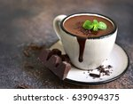 Small photo of Portion of homemade mint hot chocolate in a cup on a dark slate,stone or metal background.