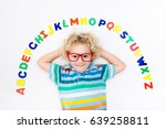 Small photo of Happy preschool child learning to read and write playing with colorful roman alphabet letters. Educational abc toys and books for kids. School student doing homework. Kid reading in kindergarten.
