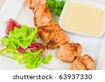 Grilled chicken kebab with sauce and greens on white plate - stock photo