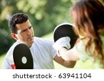 Fit woman and her trainer boxing outdoors - stock photo
