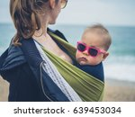 A Mother Is On The Beach With...