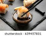 Dipping tasty roll into bowl with soy sauce on grey table, closeup