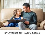 Happy Little Girl And Father Are Enjoying Reading Book Together - stock photo