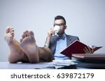 Small photo of Successful happy young businessman with bare feet working in office. (Boss, business, rules, officialdom concept)