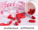 measure tape and red pills on... | Shutterstock . vector #639906244