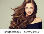 Small photo of Brunette girl with long and shiny wavy hair . Beautiful model with curly hairstyle .
