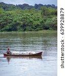 Small photo of PORTOBELO, PANAMA - CIRCA OCTOBER 2011: Man rowing a wooden boat of charcoal across the bay