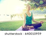 young woman doing yoga outdoors.... | Shutterstock . vector #640010959