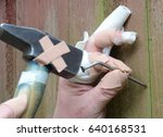 "Small photo of All thumbs, heavily ""injured"" homeworker tries to hammer a bent nail in a wall."
