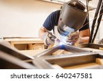 Male In Face Mask Welds With...