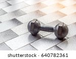 Small photo of Dumbell on ceramis background