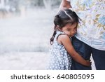 Small photo of Sad asian little girl hugging her mother leg in vintage color tone