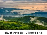 mountain ridge in fog. green rural meadow near the forest in springtime. mysterious weather at sunrise - stock photo