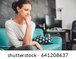 sad woman sitting on a sofa in... | Shutterstock . vector #641208637