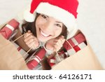 Woman shopping for christmas gifts. Young asian caucasian girl looking up smiling with shopping bags and santa hat. Copy space on the side. - stock photo