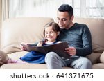 Little Girl And Father Are Reading Book Together At Home - stock photo