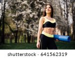 Small photo of Fitness Girl with Yoga Mat Standing Outdoor in Nature - Fit woman with exercise accessory in summertime landscape