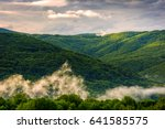 mountain ridge in fog. green forest on hillside in springtime. mysterious weather at sunrise - stock photo