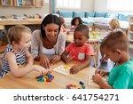 Teacher And Pupils Using Woode...