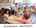 teacher and pupils working at... | Shutterstock . vector #641754379