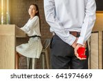 Small photo of Man holding box with marriage ring making propose to his girlfriend, Love and marriage concept, Selective focus