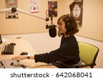 Small photo of Portrait of happy young female radio host broadcasting in studio