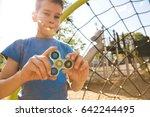 boy holds a spinner fidget in... | Shutterstock . vector #642244495