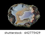 Small photo of A cross section of the agate stone. Blue-green chalcedony and quartz, on the left is a pseudo-morph. Silica bands colored with metal oxides are visible. Origin: Asni, Atlas Mountains, Morocco.