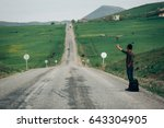 Small photo of Mus, Turkey - 4 May 2017. A guy hitchhiking down side of the road in Mus - Turkey