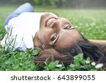 happy woman lying on the grass | Shutterstock . vector #643899055