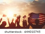 Small photo of Patriotic holiday. Silhouettes of people holding the Flag of USA. America celebrate 4th of July.
